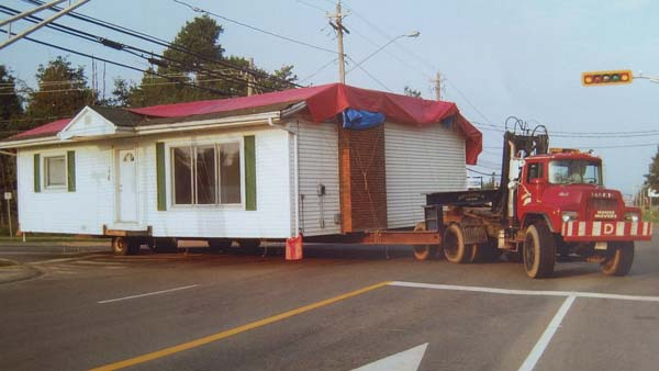 truck pulling a white bungalow house on street